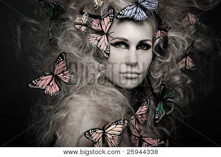 Beautiful young woman with butterfly in big curly hair on black.
