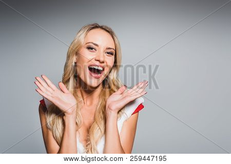Happy Attractive Woman In Christmas Dress Doing Shrug Gesture Isolated On Grey Background