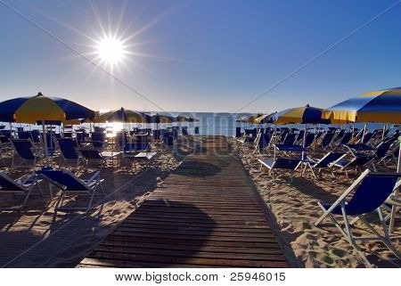 Empty beach with umbrellas and sun shortly after the sunrise