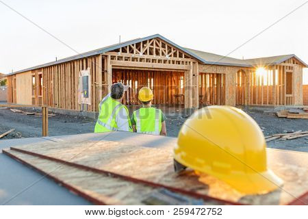 Male and Female Construction Workers at New Home Site.