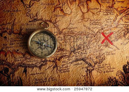 Old brass compass lying on a very old map showing the way to treasure