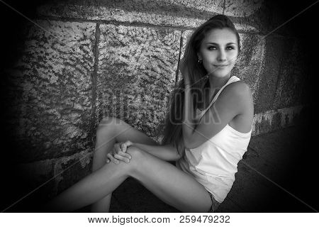 Portrait Of Sexy  Slender Young Woman In White T-shirt, Sitting Near Wall In An Erotic Pose. Attract