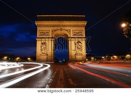 Beautifly lit Triumph Arch at night with light traces of passing cars. Paris, France.
