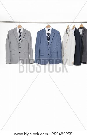 Row of five man suit ,Shirts with ties on hangers