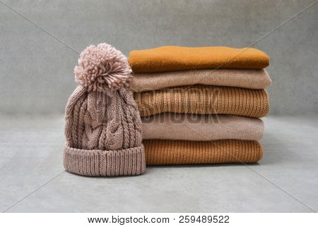 knitted Hat on Stack of knitted sweaters-gray \ background