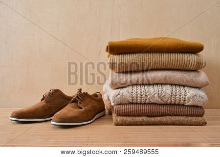 Stack of knitted sweaters with brown shoes-wooden background