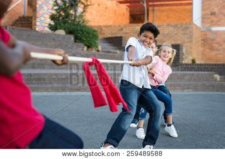 Happy group of kids playing tug of war outdoor. Young boys and girls as a team in tug-of-war outside the school. Group of happy multiethnic friends playing with rope in city park.