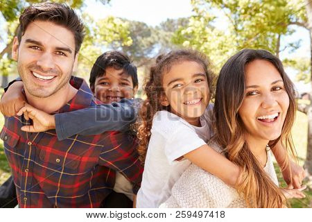 Young parents piggybacking their two kids outdoors