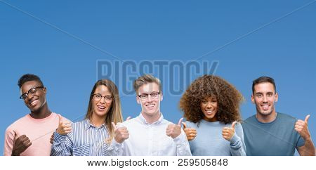 Composition of group of friends over blue blackground success sign doing positive gesture with hand, thumbs up smiling and happy. Looking at the camera with cheerful expression, winner gesture.