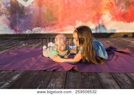 Cute Child Baby Boy And Little Girl Lying On Blanket In Summer Day On Nature. Brother And Sister Con