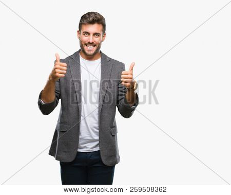 Young handsome business man over isolated background success sign doing positive gesture with hand, thumbs up smiling and happy. Looking at the camera with cheerful expression, winner gesture.