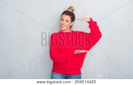 Young adult woman over grey grunge wall wearing winter outfit gesturing with hands showing big and large size sign, measure symbol. Smiling looking at the camera. Measuring concept.