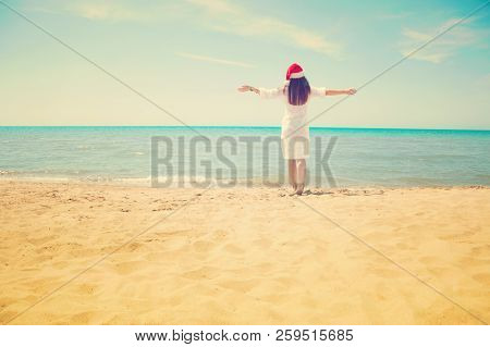 Young Woman In Santa Hat On Tropical Beach. Christmas Vacation. Christmas Beach Vacation Travel Woma