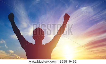 Young Man Standing With Arms Outstretched At Sunset