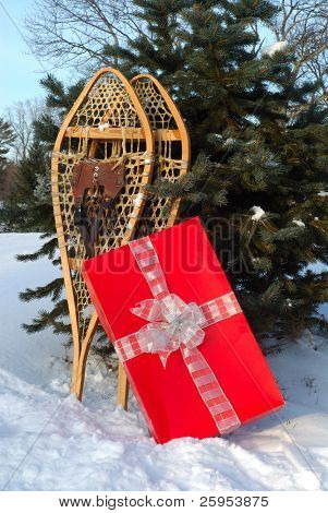 Pair Of Wooden Traditional Snowshoes With A Red Gift Box In The Snow