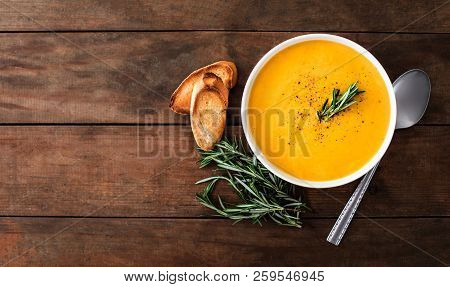 Pumpkin And Carrot  Cream Soup On Rustic Wooden Table. Autumn Pumpkin Cream-soup With Rosemary Herb