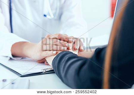 Friendly Female Doctor's Hands Holding Female Patient's Hand For Encouragement And Empathy Close-up.