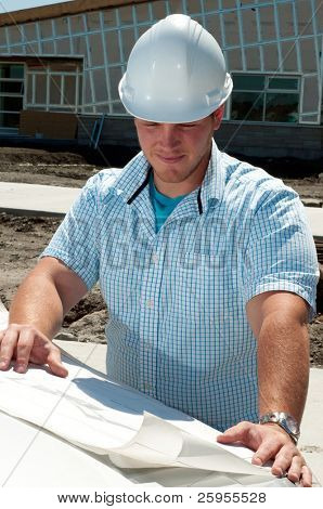 Young Building Contractor Checking The Plans To A New Commercial Building
