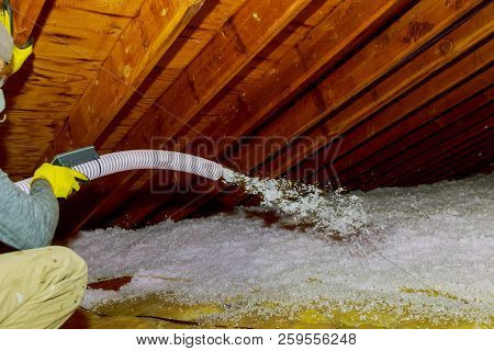 Technician Spraying Blown Fiberglass Insulation Between Attic Trusses Foam Insulation Repair Tool In