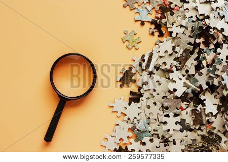Pieces Of Jigsaw Puzzle With Magnifying Glass On Beige Color Background For Analysis And Problem Sol