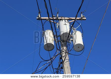 Electrical Transformers Stand In Stark Contrast To The Clear Blue Skies In This Rural Town