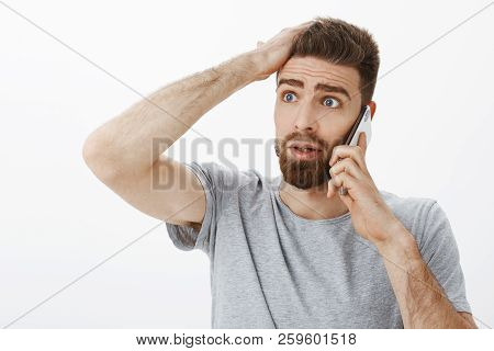 Concerned and troubled anxious boyfriend receiving bad news during phone call holding arm on forehead looking left concerned and clueless standing confused and perplexed over gray wall poster
