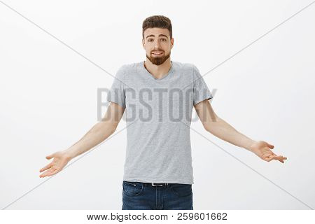 Waist-up Shot Of Carefree Clueless And Unconcerned Cute Man With Blue Eyes And Beard Shrugging With