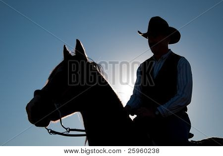 Rider in a cowboy hat and a horse silhouetted against sun and clear blue sky poster