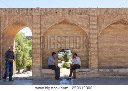 Isfahan, Iran - August 7, 2015: Senior Iranian People, Men, Sitting And Discussing On The Archs Of T