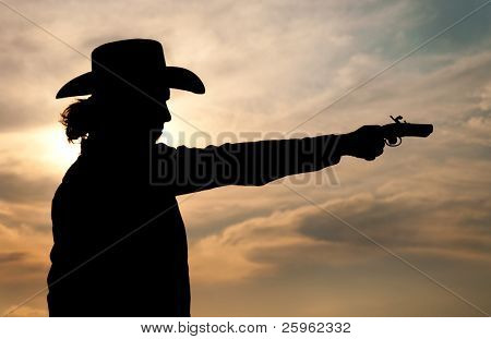 Silhouette of a young man in a cowboy hat shooting an antique hand gun