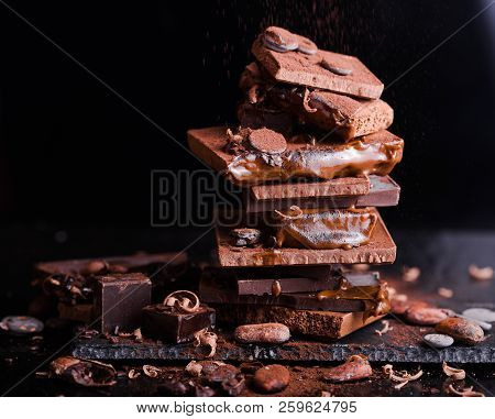 Assorted Stack Chocolate Candies. Chocolate Sweets. Candy Design Over Dark Brown Background. Various