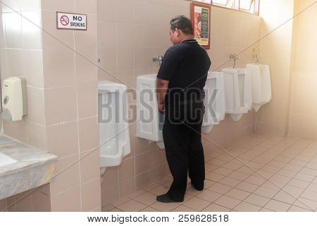 Tak,thailand,21 Sep 2018, The Man In Black Standing For Urinal Pissing At Urine Bidet Within  The Pu