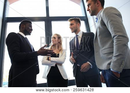 Young Modern Colleagues In Smart Casual Wear Having A Brainstorm Meeting While Standing In The Creat