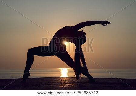 Woman Doing Power Pilates Or Hatha Yoga With A Beautiful View. Concept Of Yoga Teaching Outdoors. He