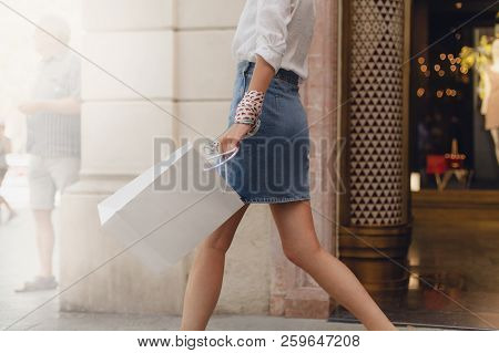 Crop Picture Of Girl Walking With Shopping Bag On City Streets While Doing Shopping. Stylish Girl Wa