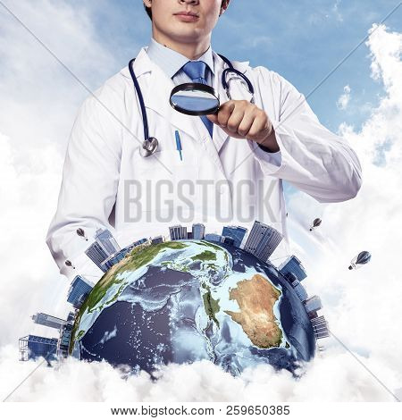 Cropped image of professional man doctor in white suit and stethoscope on neck discovering Earth globe through magnifier, with cloudy skyscape on background. Medical industry concept. Elements of this image furnished by NASA poster