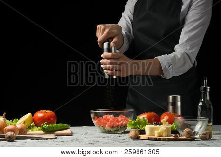 The Chef Prepares A Salad, With A Pepper Mill On A Dark Background With An Empty Space For Writing