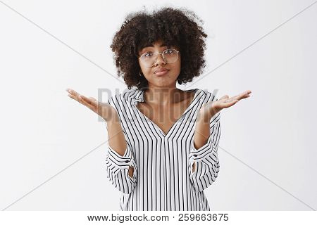 Waist-up Shot Of Upset Woman Losing In Battle Shrugging With Spread Palms Aside Pursing Lips And Fro
