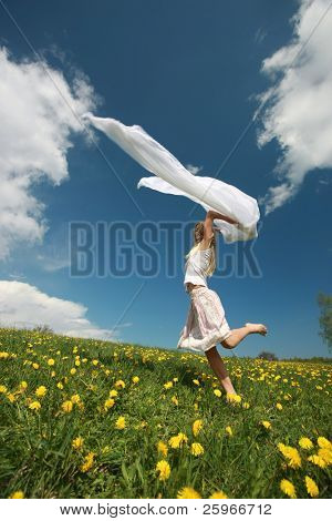 Girl jumps over dandelion field in nice summer day