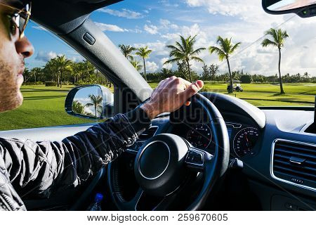 poster of Male hands holding car steering wheel. Hands on steering wheel of a car driving. Young Man driving a car inside cabin. Multimedia system. Man Traveling In Self Driving Car. Car inside.