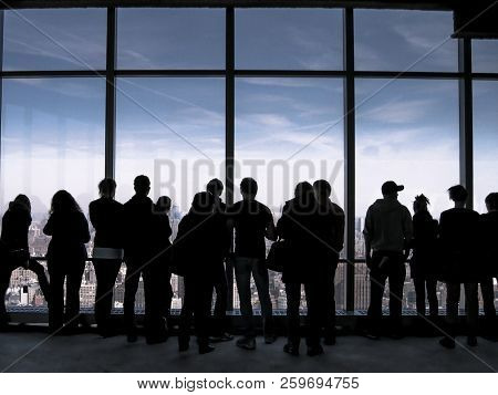 Silhouette Of Young People Looking Through Full-length Window At Urban Cityscape, With Concept Of Am