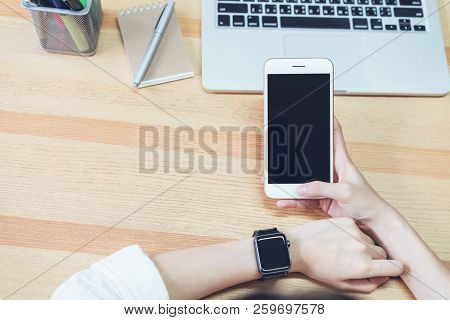 Photo Of A Woman Holding A Blank Screen Phone And A Computer. And Put A Smart Watch. Concept Technol