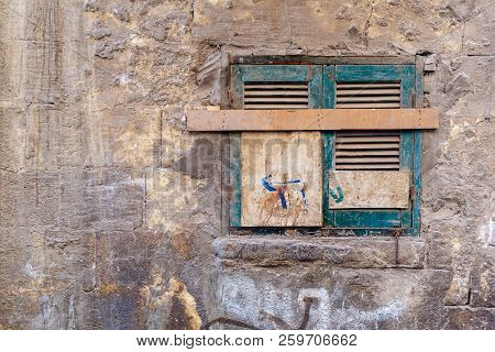 Old Grunge Window With Closed Green Broken Shutters On Dirty Cracked Bricks Stone Wall