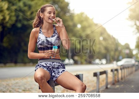 Sporty Attractive Slender Young Woman Sitting On A Roadside Rail Eating A Piece Of A Protein Bar As