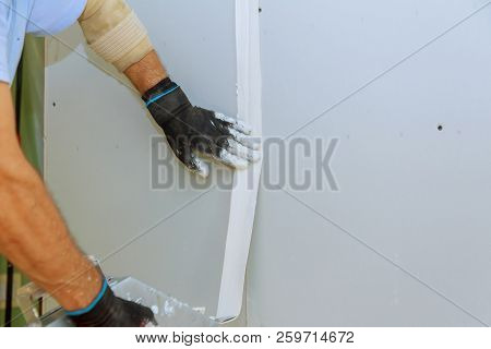 Repair work and construction worker in overalls plastering a wall with finishing putty using a putty knife. poster