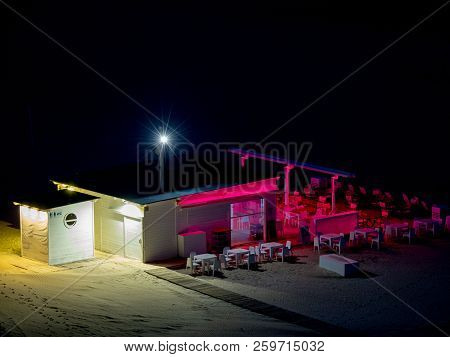 Empty Beach Bar With Bar And Chairs And Tables Lit With Pink And White Lights At Night On The Beach