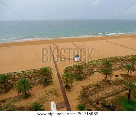 Aerial View Of Gandia Beach In Spain, With Wooden Footbridges Palm Trees And Vegetation And With Spo