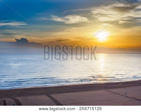 Sunrise Are The Sun Low On The Horizon And Reflections In The Sea At The Beach Of Gandia, Spain In T