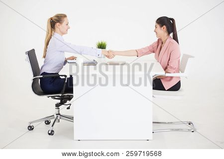 Two Businesswomen In Suits Sitting Between The Table Handshaking Of Deal On White Background. Human