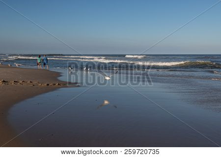 Avon By The Sea, New Jersey-september 16: A Couple Walks Hand And Hand Along The Beach On September